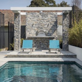 stone clad wall pizza oven pool lounge