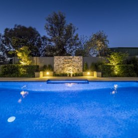 swimming pool raised garden beds lighting stone water feature wall
